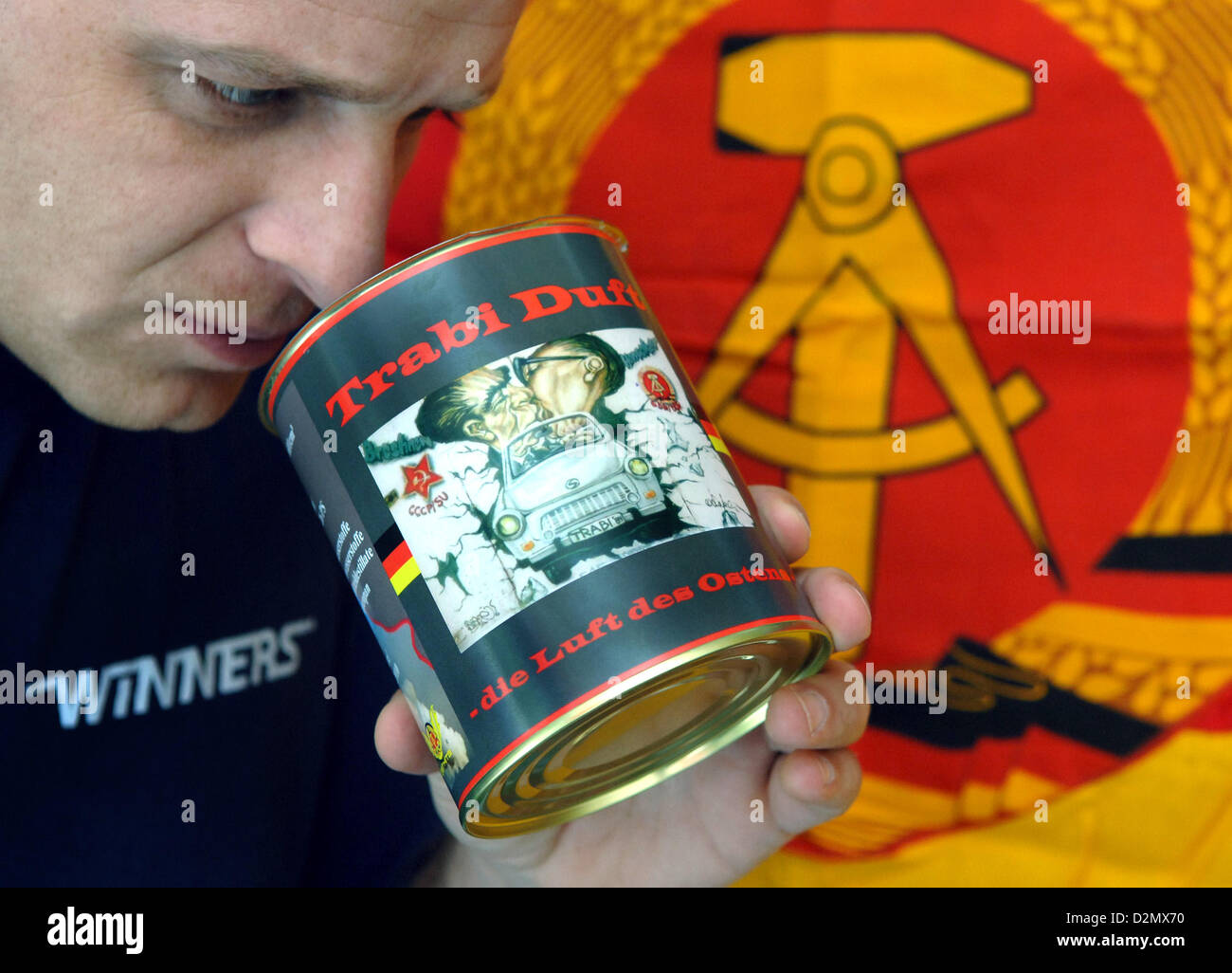"""Employee Andreas Weißbeck of Osthits.de smells at a can with """"Trabi Duft"""" (""""Trabant smell"""") in front of a GDR flag Stock Photo"""