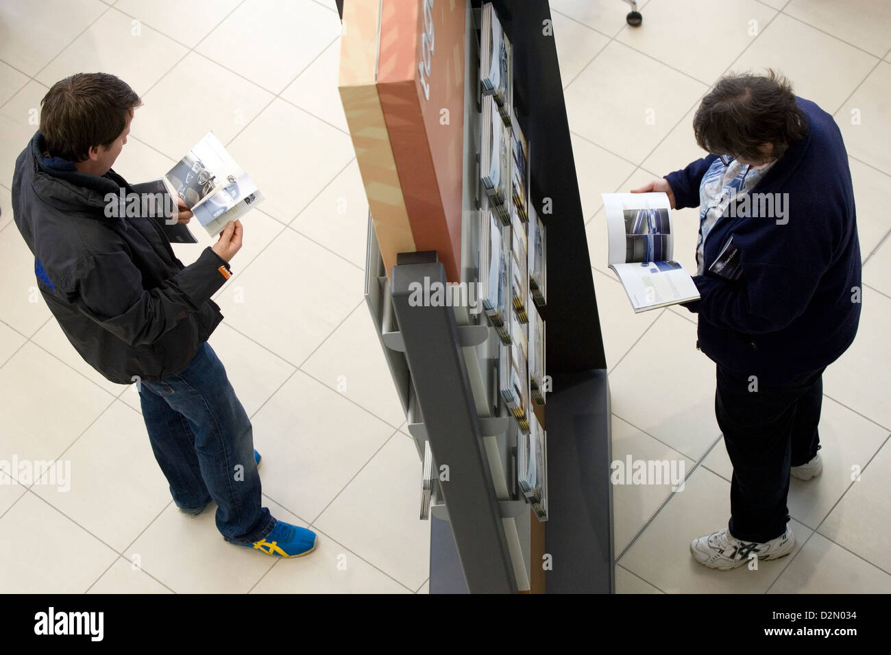 People reading brochures in a car dealership showroom. - Stock Image