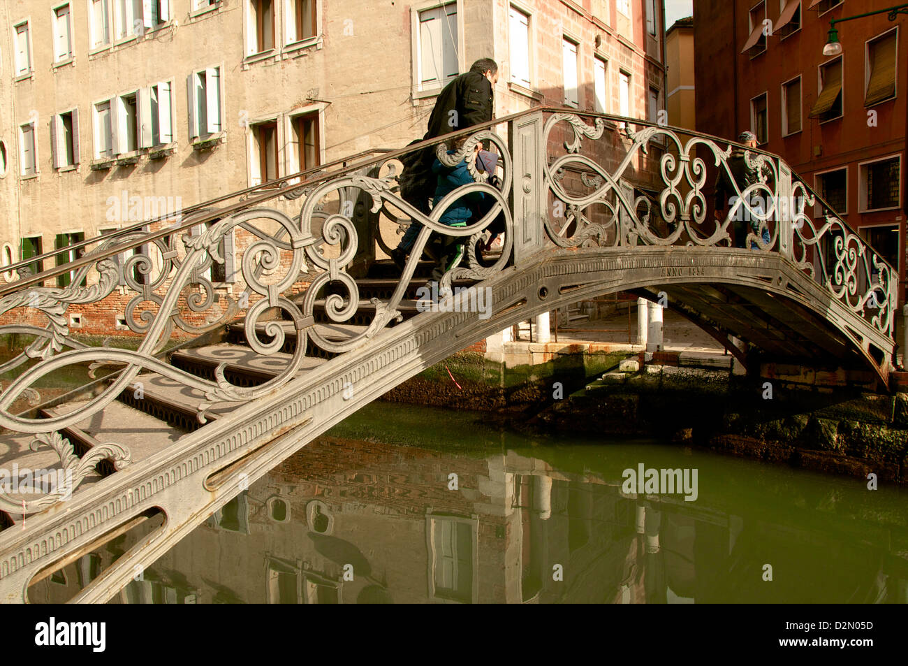 Exceptional metal bridge over canal with water reflections, and pedestrian, Venice, Veneto, Italy - Stock Image