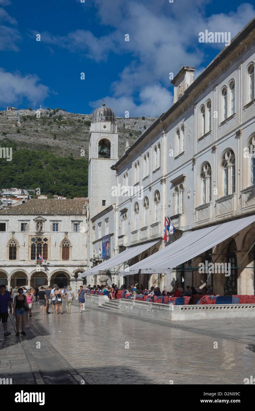 Street with cafes, foot worn polished pavement and the Clock Tower, Old City, Dubrovnik, Croatia - Stock Image