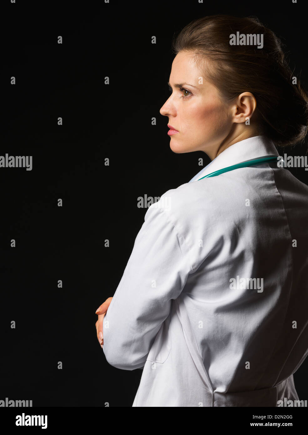 Portrait of confident medical doctor woman looking on copy space isolated on black - Stock Image