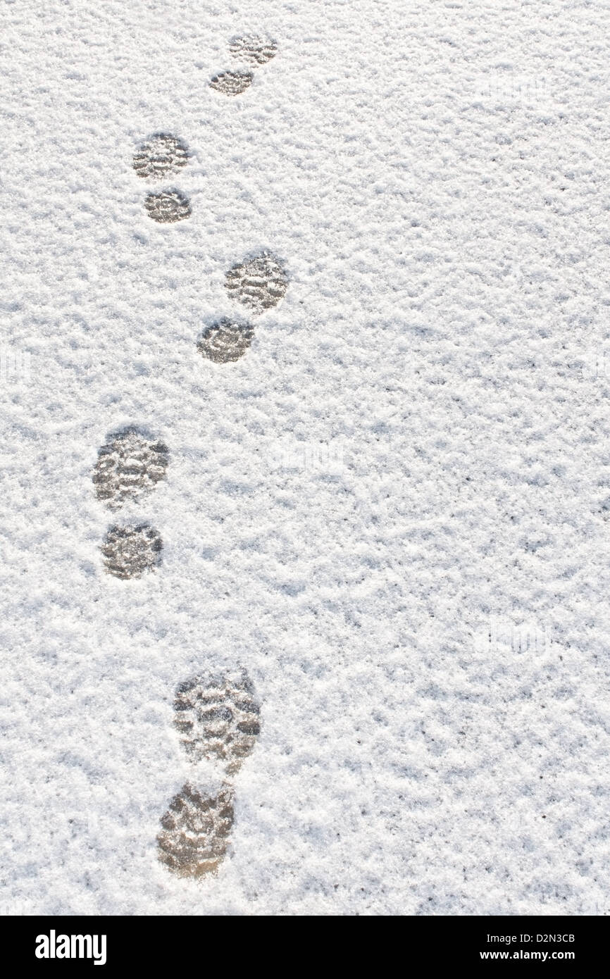 Footprints in fresh snow background great concept for winter footwear - Stock Image