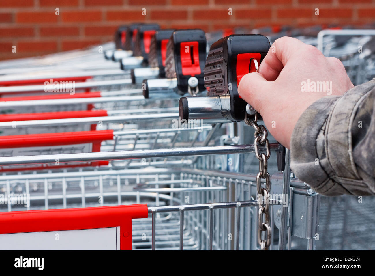 Inserting coin or token into shopping cart at the superstore - Stock Image