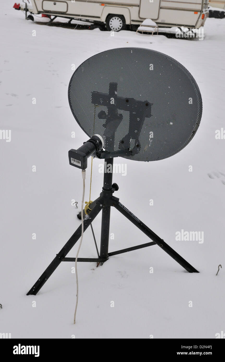 A satellite dish supplying  signals to caravan in an all season caravan park photographed during january's snow - Stock Image