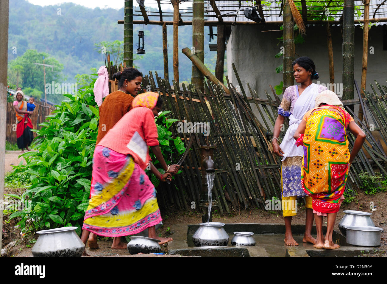 Women pumping water from a hand pump, Jorhat, Assam, India, Asia - Stock Image