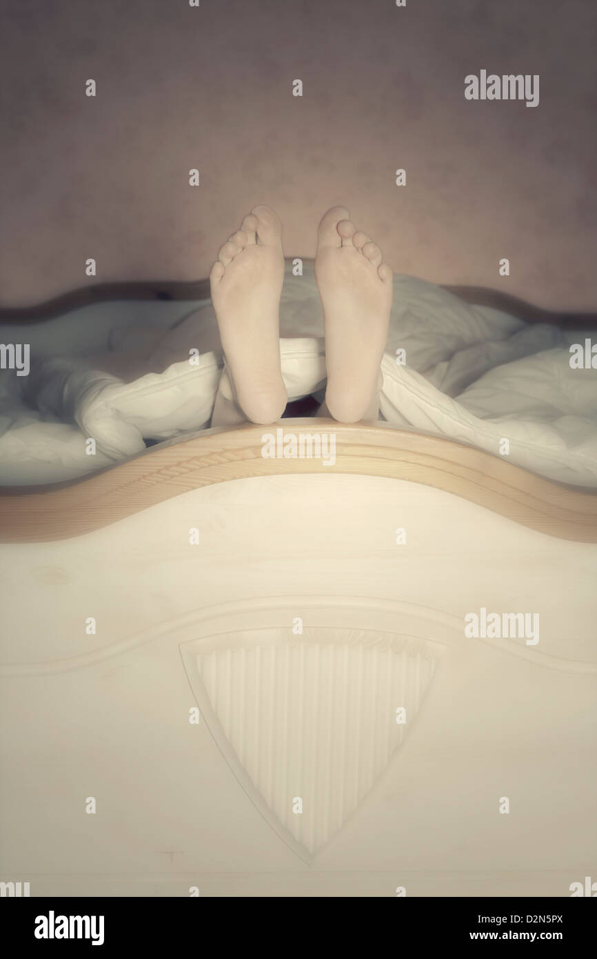female feet in a bed - Stock Image