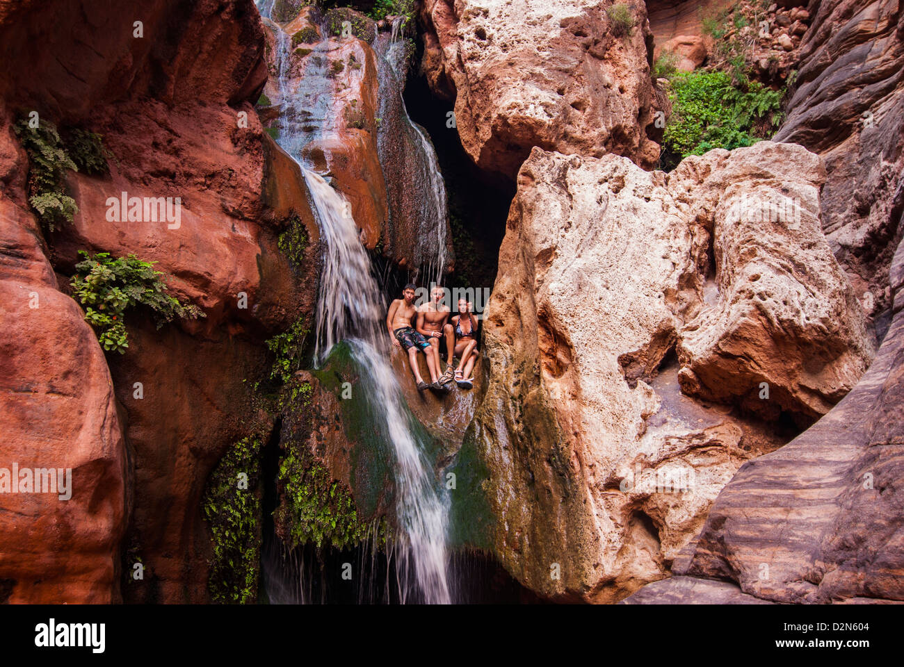 Tourists bathing in a waterfall, seen while rafting down the Colorado River, Grand Canyon, Arizona, USA - Stock Image