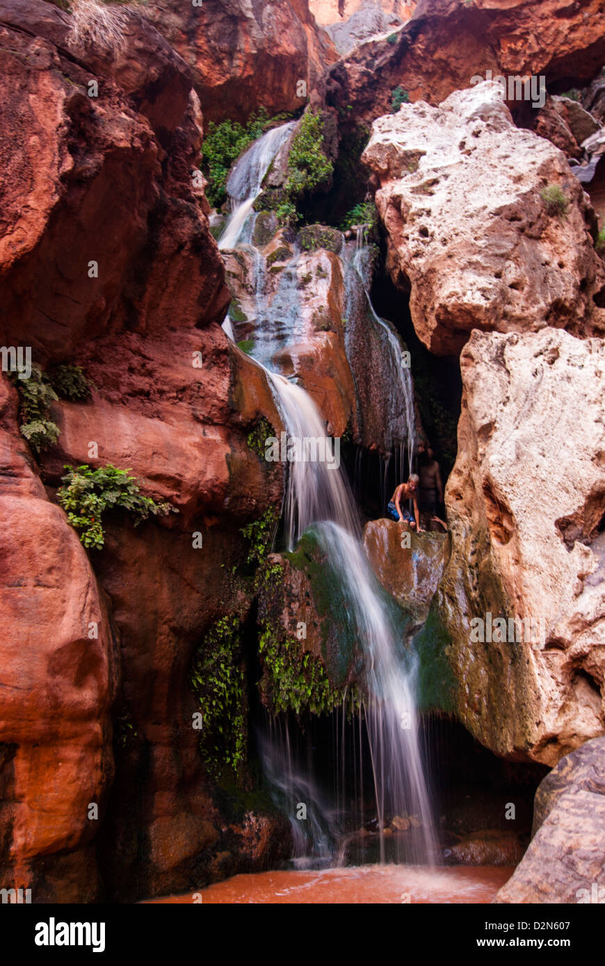 Tourist bathing in a waterfall, seen while rafting down the Colorado River, Grand Canyon, Arizona, USA - Stock Image