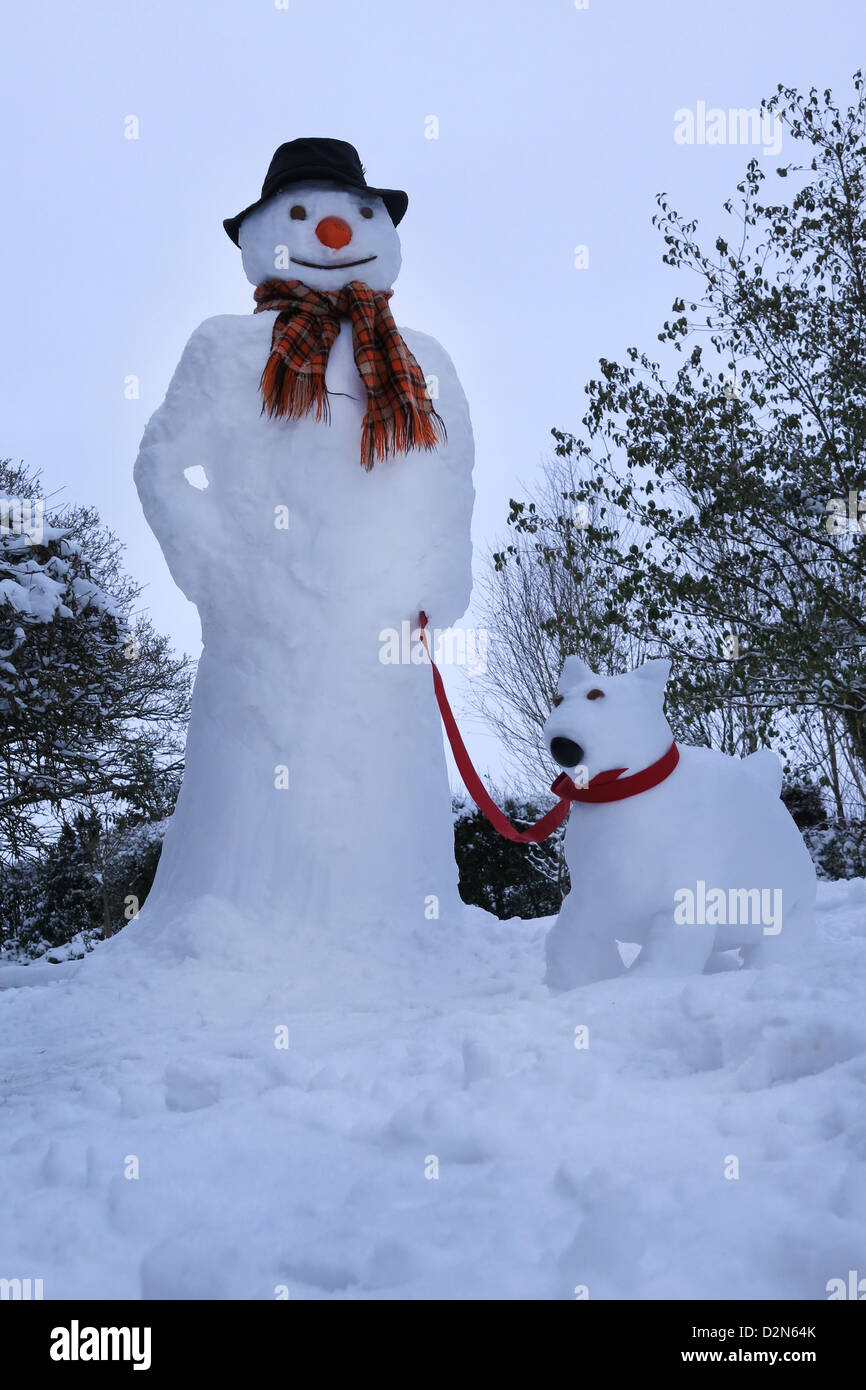 A Snowman with a snow dog - Stock Image