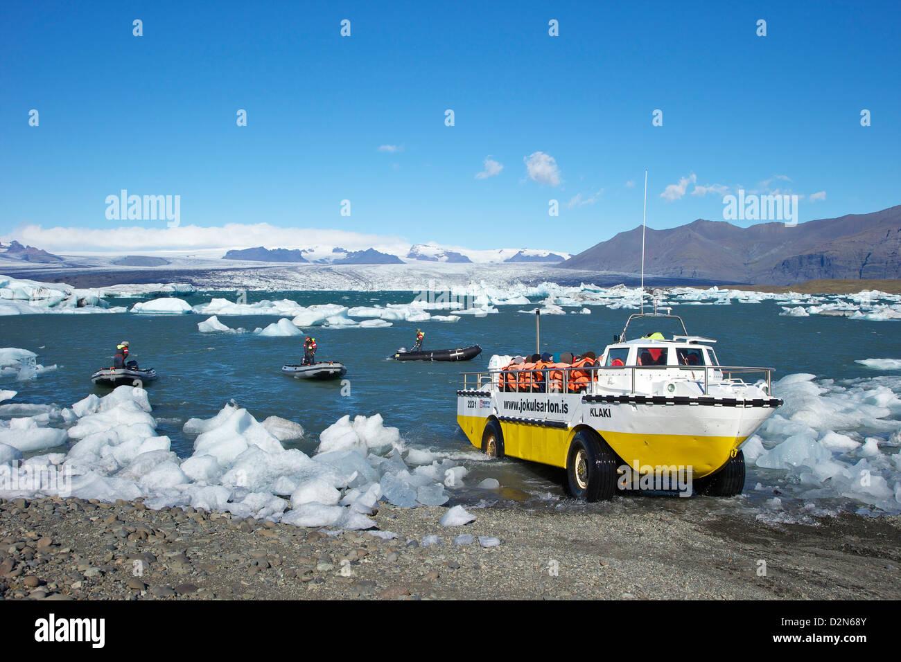 Amphibious boat and icebergs on glacial lake at Jokulsarlon with icecap of Vatnajokull behind, Iceland, Polar Regions - Stock Image