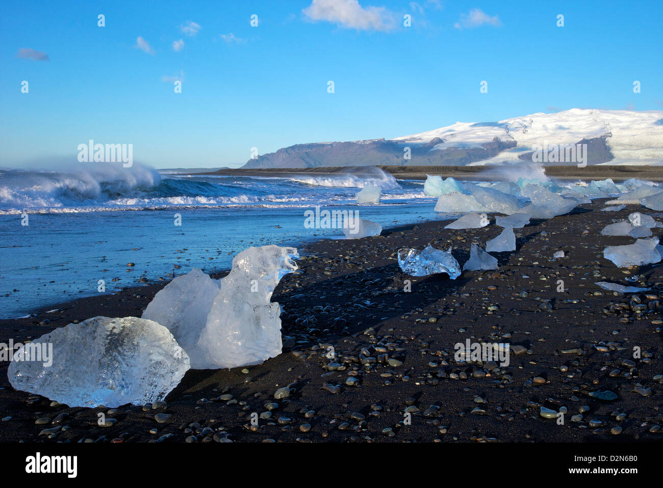 Icebergs on volcanic sand beach at Jokulsarlon with snow on the massive icecap of Vatnajokull behind, Iceland, Polar - Stock Image