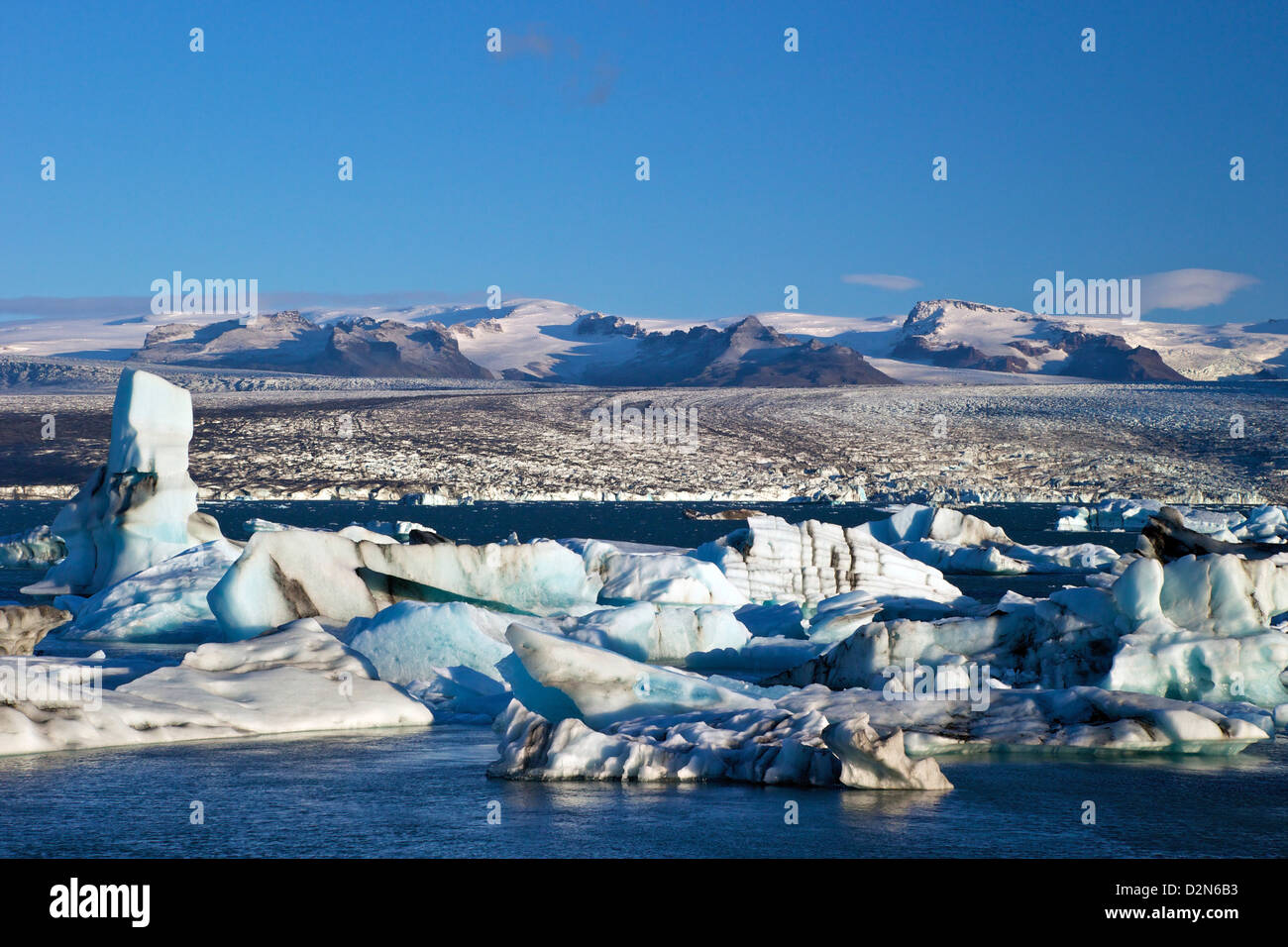Icebergs on glacial lake at Jokulsarlon with snow on the massive icecap of Vatnajokull behind, Iceland, Polar Regions - Stock Image