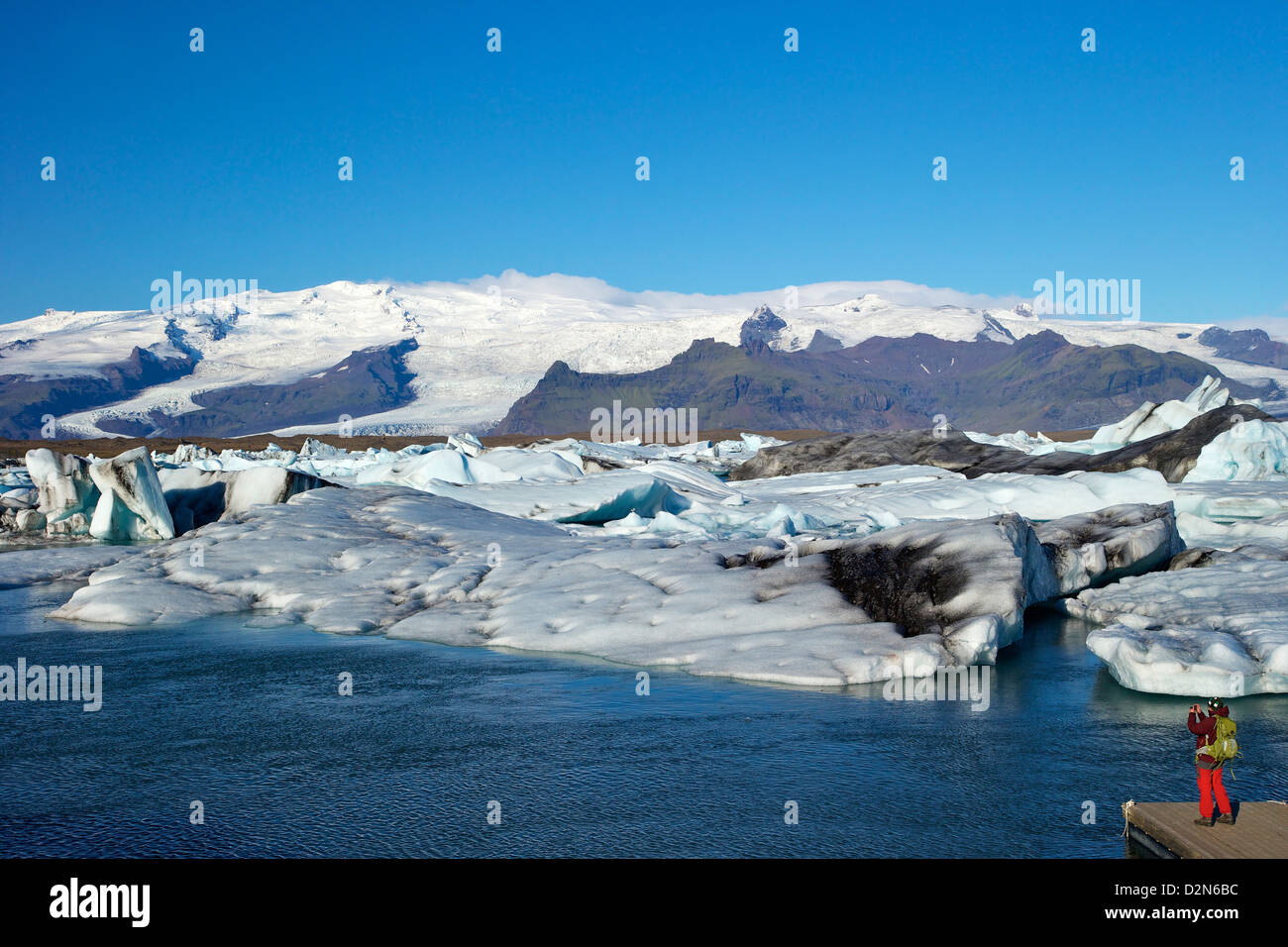 Man taking photo of icebergs on the glacial lake at Jokulsarlon icecap of Vatnajokull behind, Iceland, Polar Regions - Stock Image