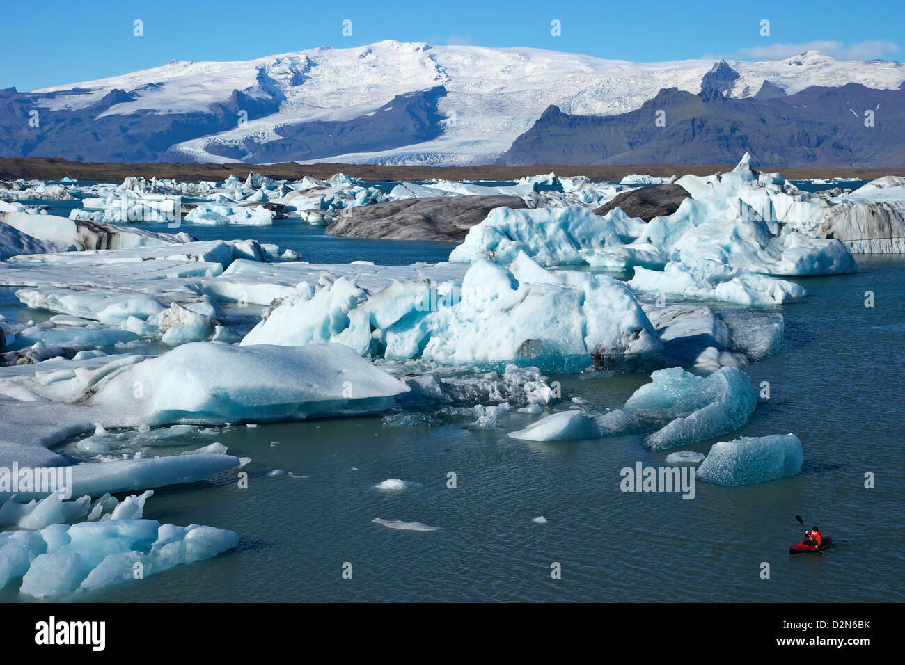 Canoeist paddles between icebergs on glacial lake at Jokulsarlon with the icecap of Vatnajokull behind, Iceland, - Stock Image