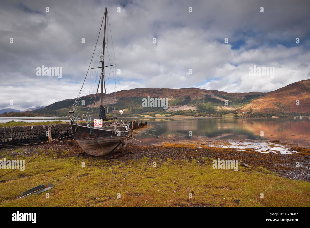 An old boat sits on the shore of Loch Leven in Glencoe, Highlands, Scotland, United Kingdom, Europe - Stock Image