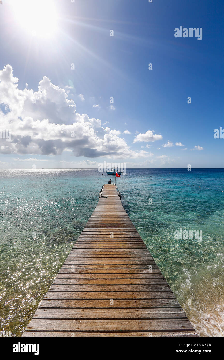 View over a wooden pier, island warm waters at the Caribbean island of Curacao - Stock Image