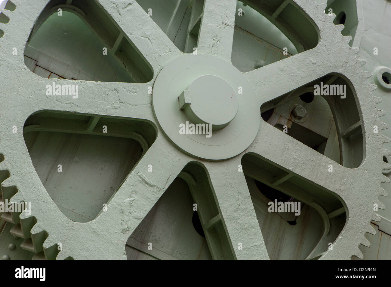 A large green cog wheel in a naval dockyard - Stock Image