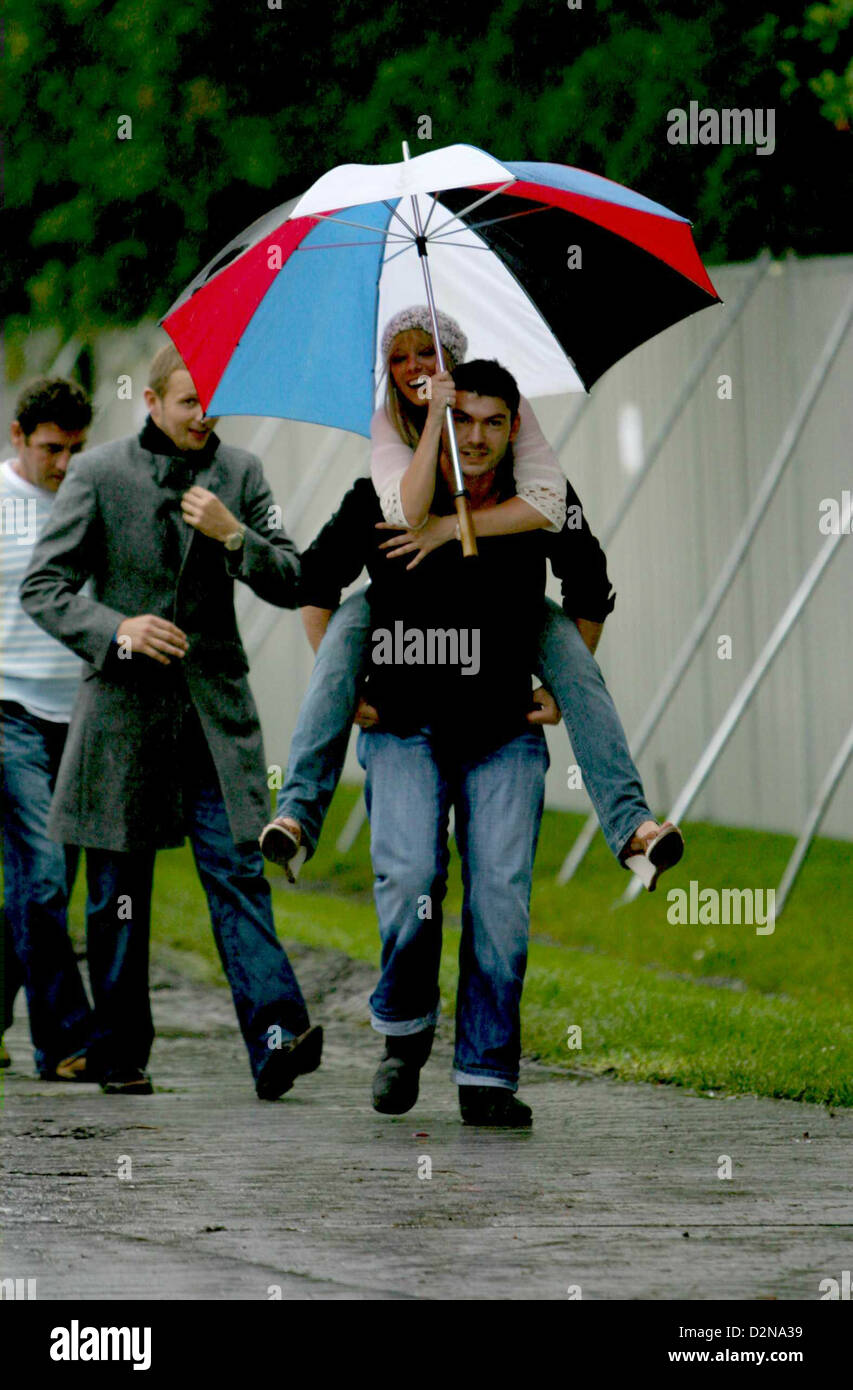 Former Atomic Kitten singer Liz McClarnon gets a piggy back to the stage through the rain. - Stock Image