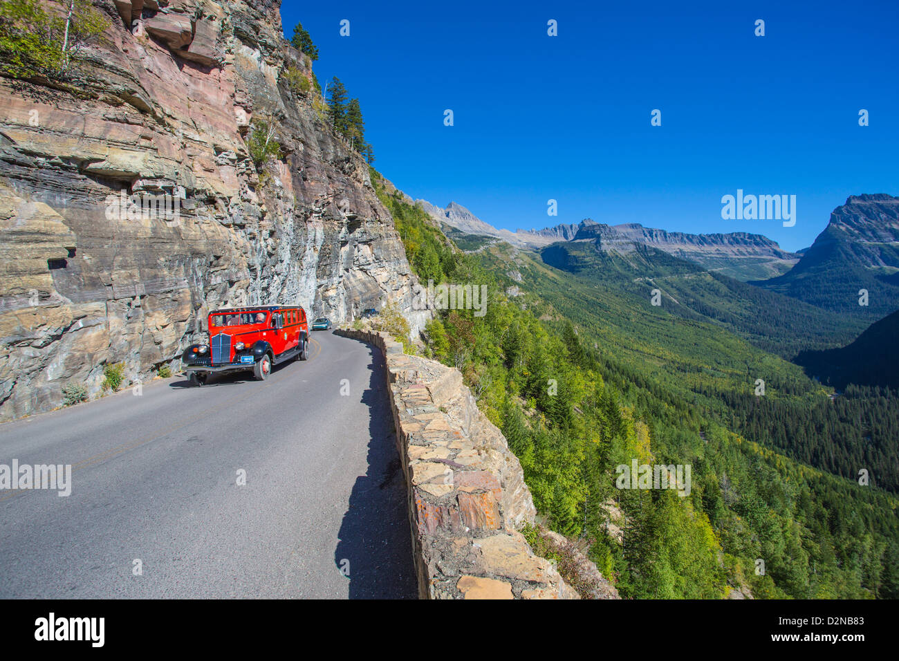 Red Bus on the Going to the Sun Road in Glacier National Park in the Rocky Mountains of Montana - Stock Image