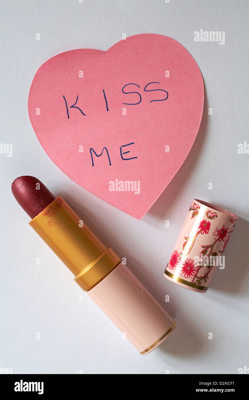 kiss me message written on pink heart shaped post it note pad with lipstick isolated on white background Stock Photo