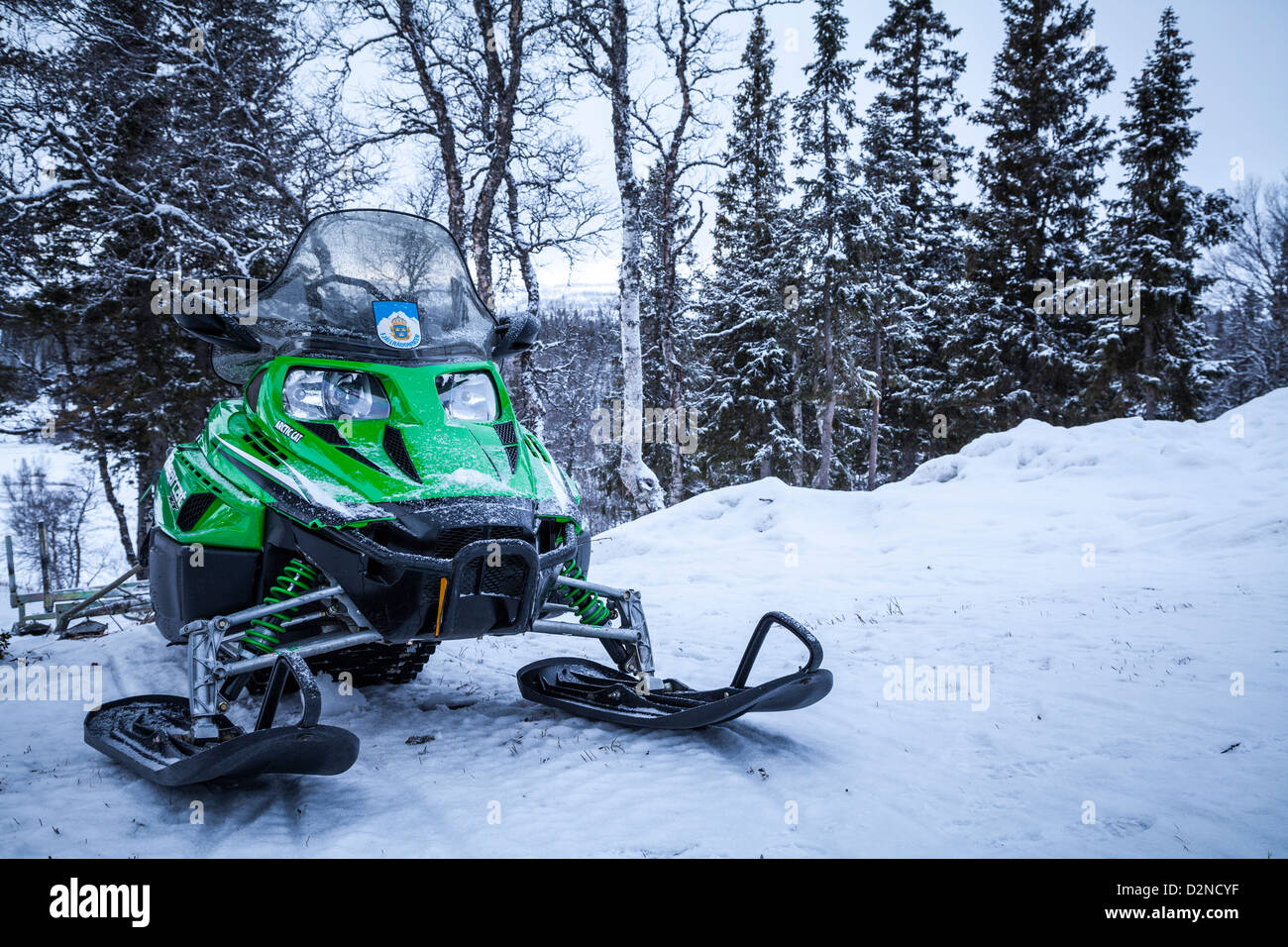 Snowmobile with snow-covered trees in the background, Sweden - Stock Image