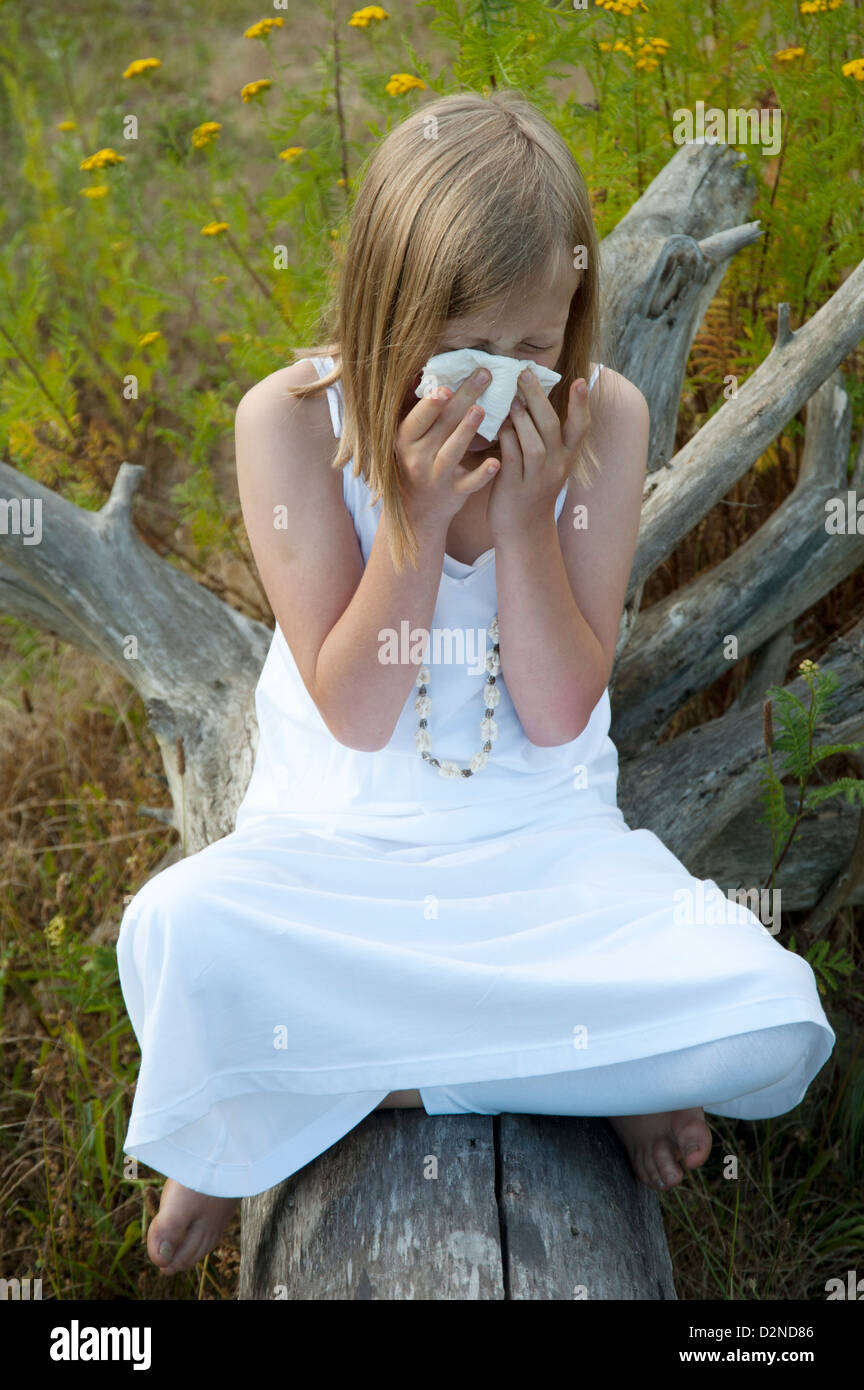 Young girl outdoors sneezing, blowing her nose and suffering from allergies - Stock Image