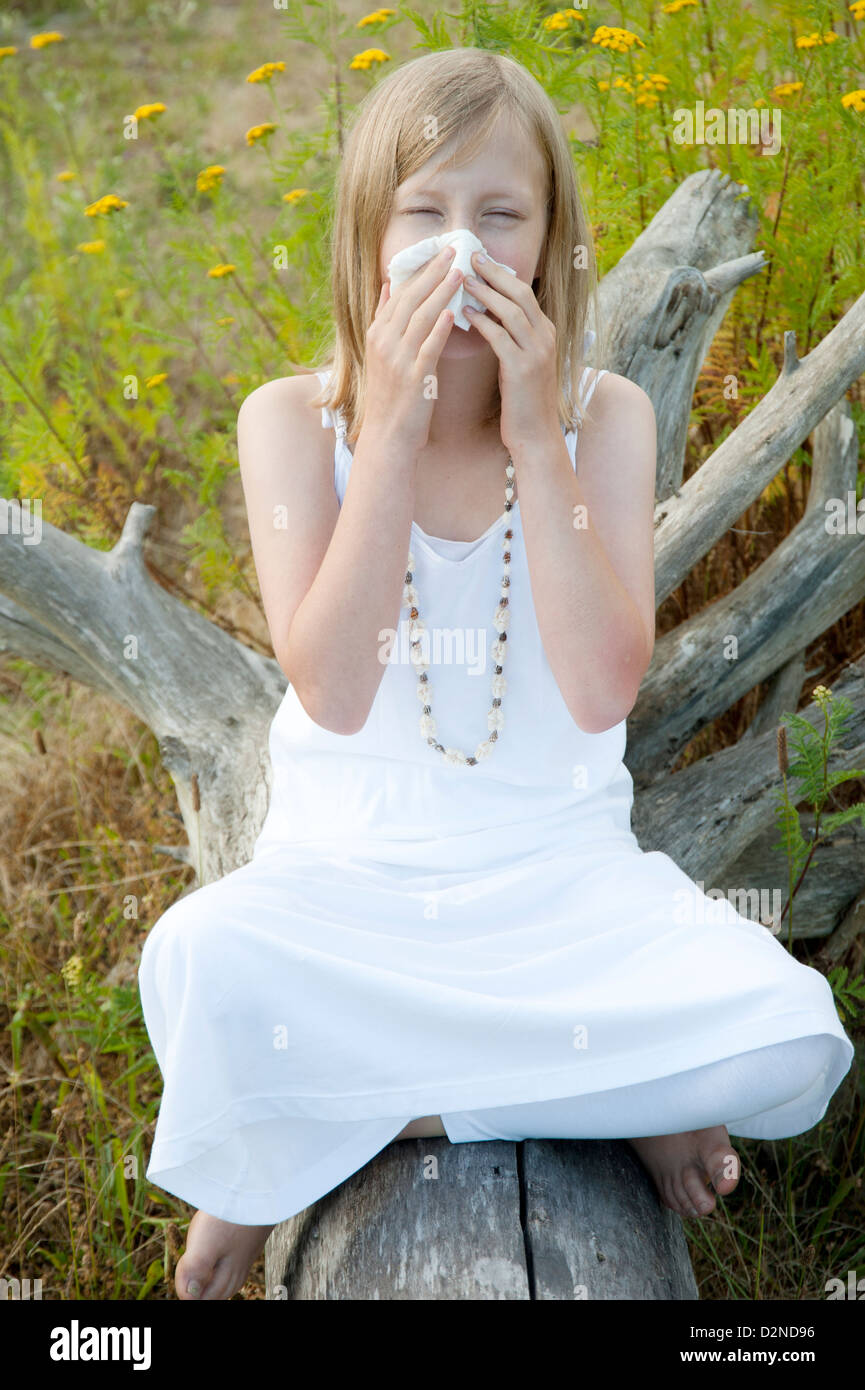Young girl sitting on a log in summer surrounded by weeds and blowing her nose because of allergies - Stock Image