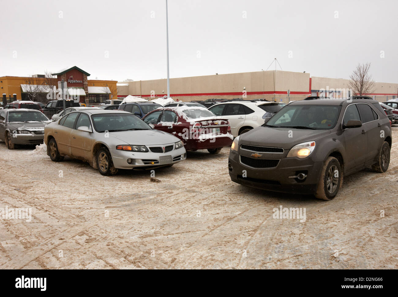 drivers trying to find parking place in snow covered outdoor parking lot Regina Saskatchewan Canada - Stock Image