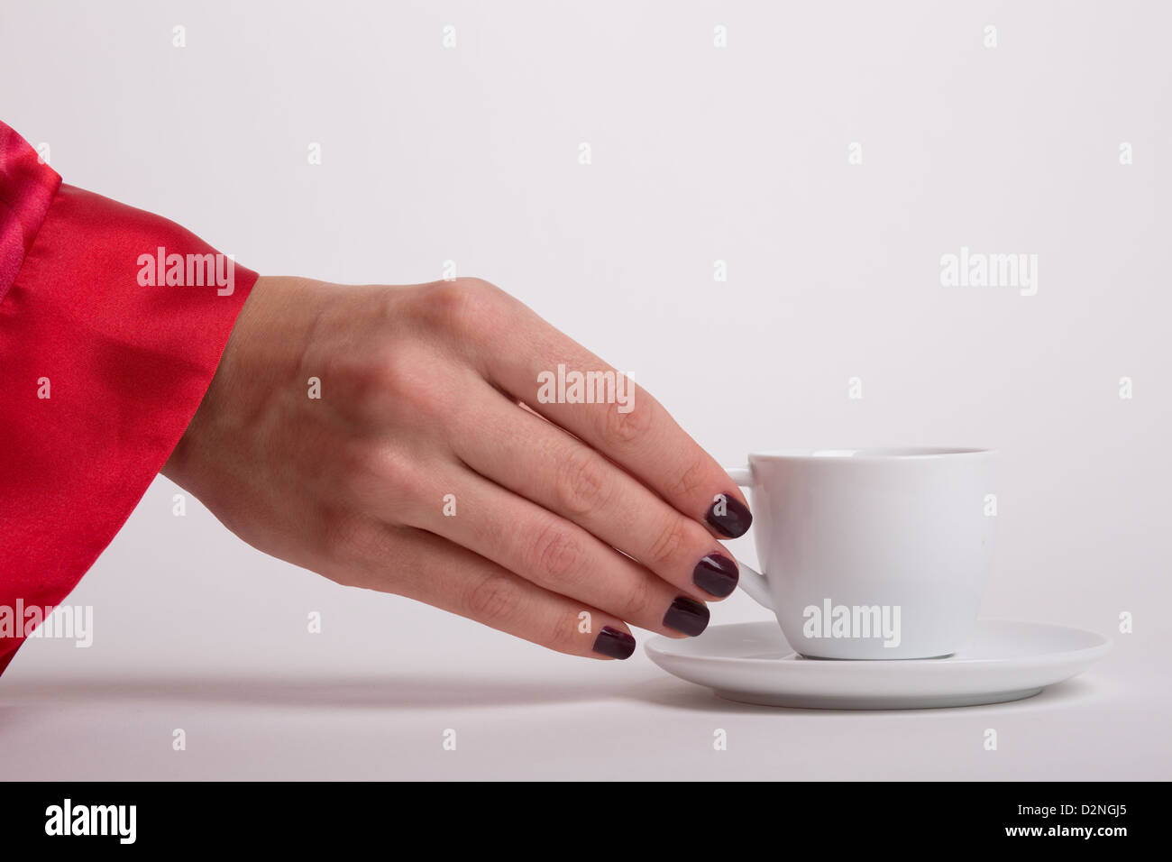 A woman wearing a red robe is reaching out for a morning white cup of espresso Stock Photo