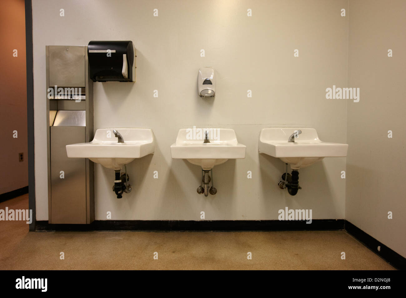 row of sinks in mens washroom High school canada north america - Stock Image