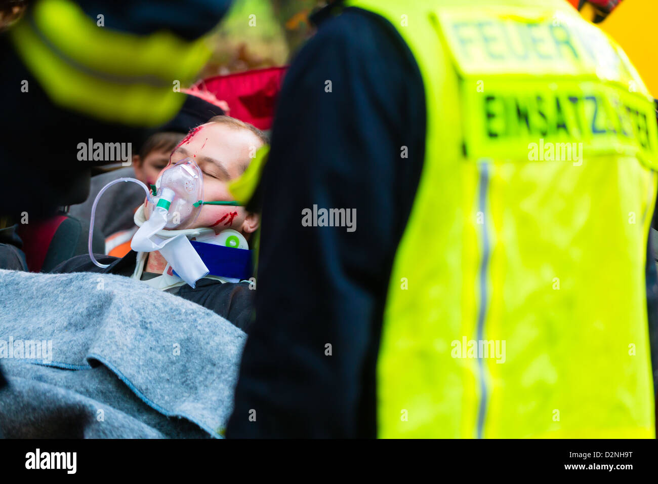 Accident - Fire brigade and Rescue team pulling cart with wounded person wearing a neck brace and respirator - Stock Image
