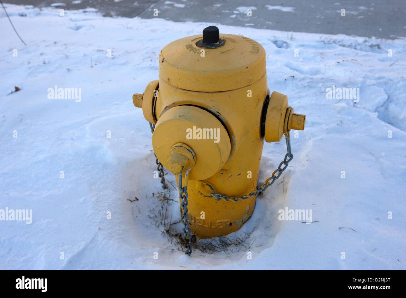 mueller yellow fire hydrant in the snow Saskatoon Saskatchewan Canada - Stock Image