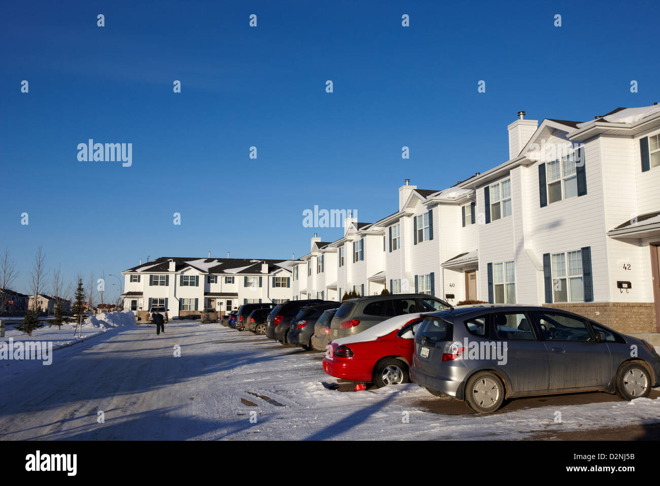 outdoor parking lot with vehicles outside row of condominium starter homes during winter Saskatoon Saskatchewan - Stock Image