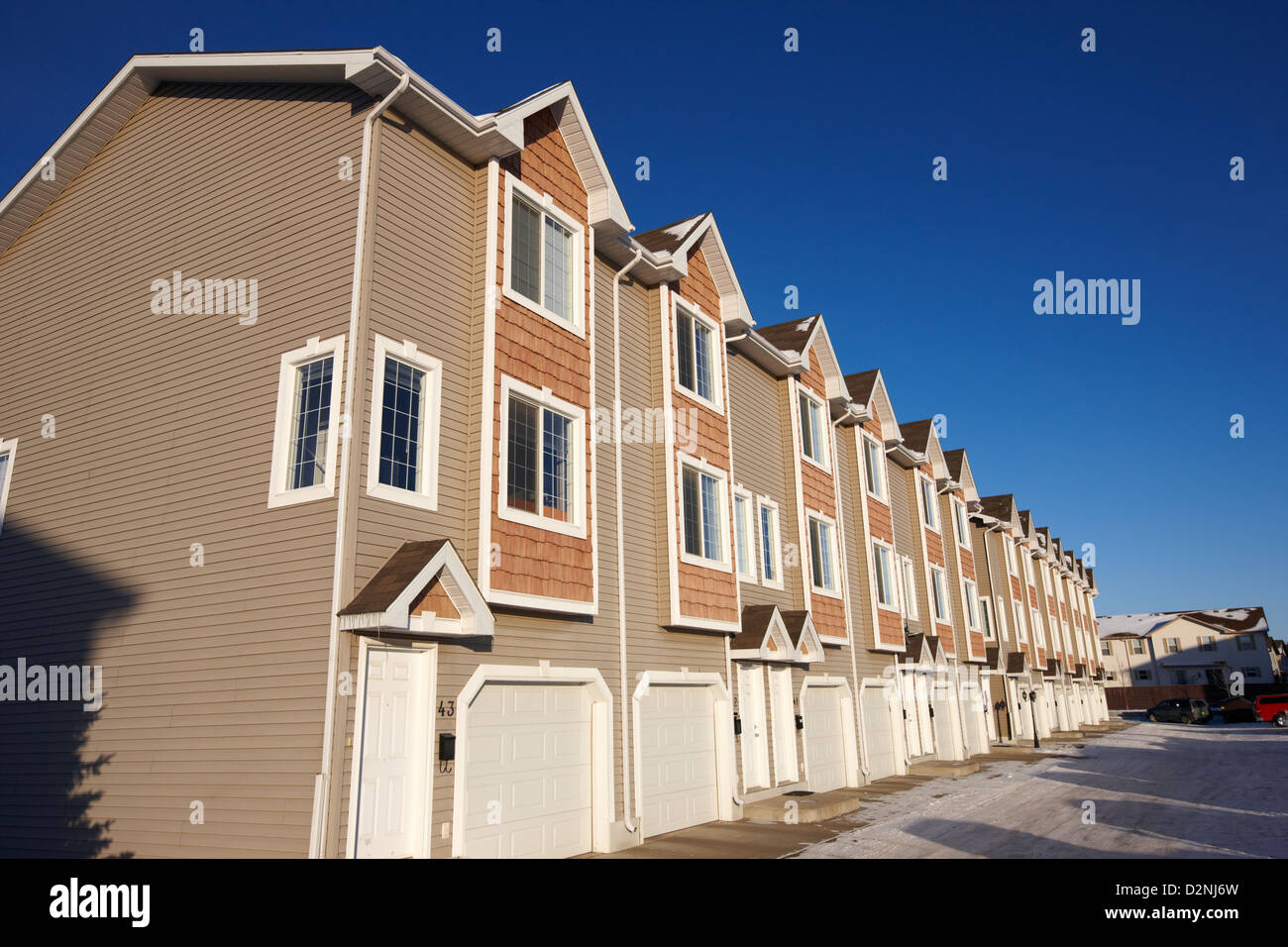 row of condominium starter homes during winter Saskatoon Saskatchewan Canada - Stock Image