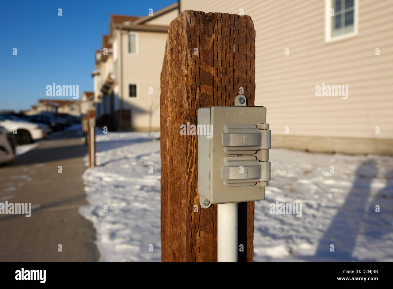 electric power connection for engine block heaters in residential parking bay outside homes in Saskatoon Saskatchewan - Stock Image