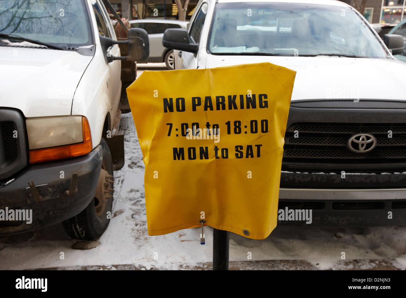 cars parked beside no parking cover on a parking meter during winter Saskatoon Saskatchewan Canada - Stock Image