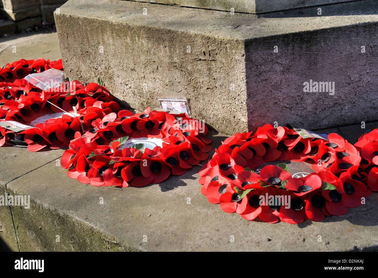 Poppy wreaths laid on war memorial - Stock Image