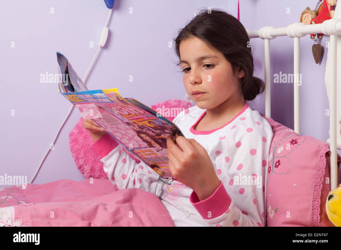 Girl reads a magazine in her bed - Stock Image