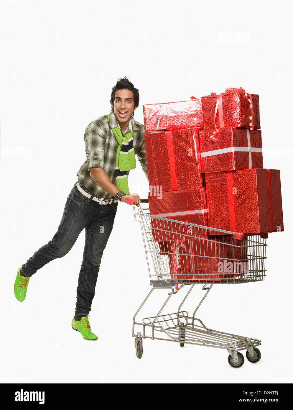 Man pushing a shopping cart filled with gifts - Stock Image