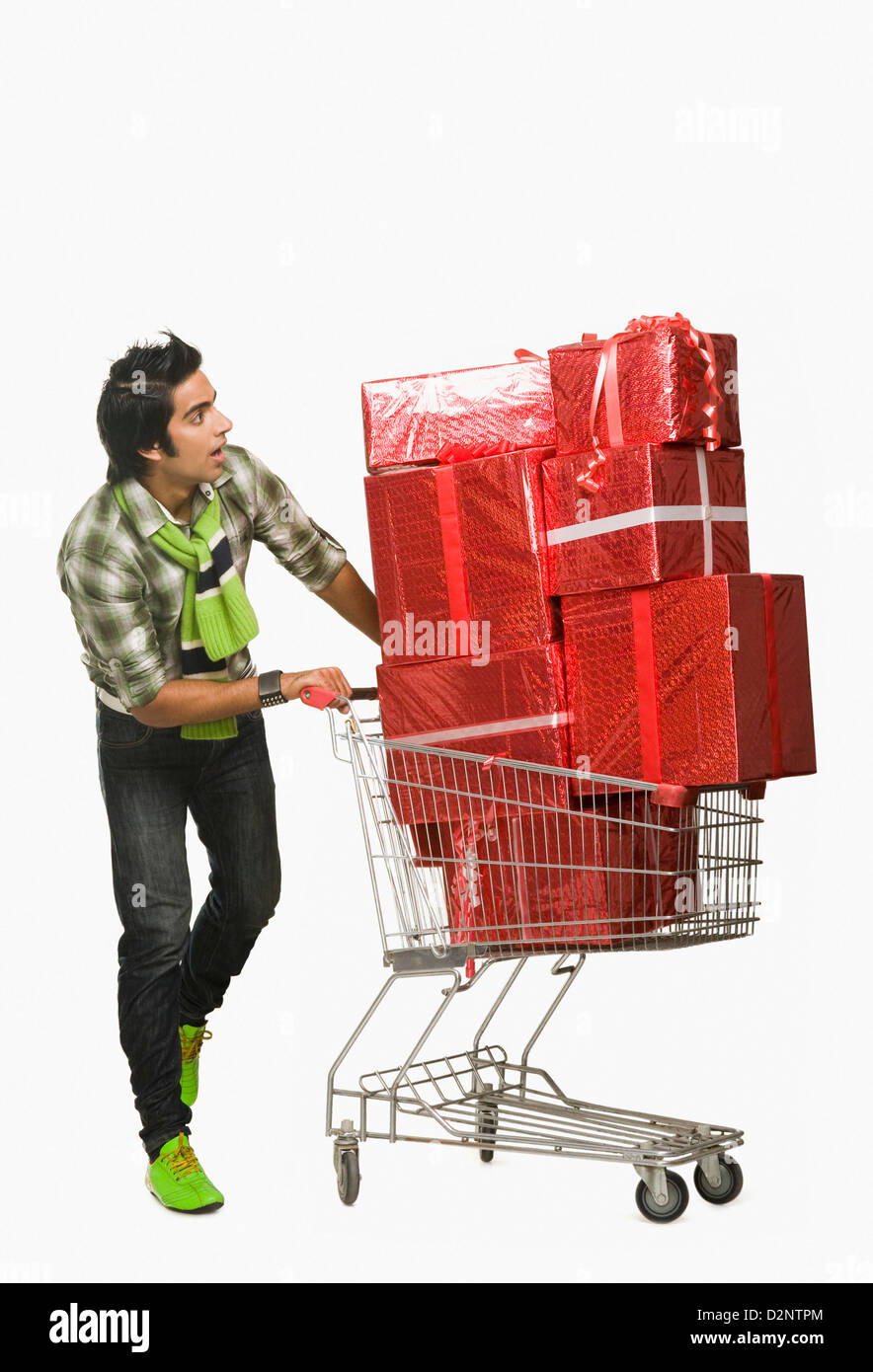Man pushing a shopping cart filled with gifts and looking surprised - Stock Image