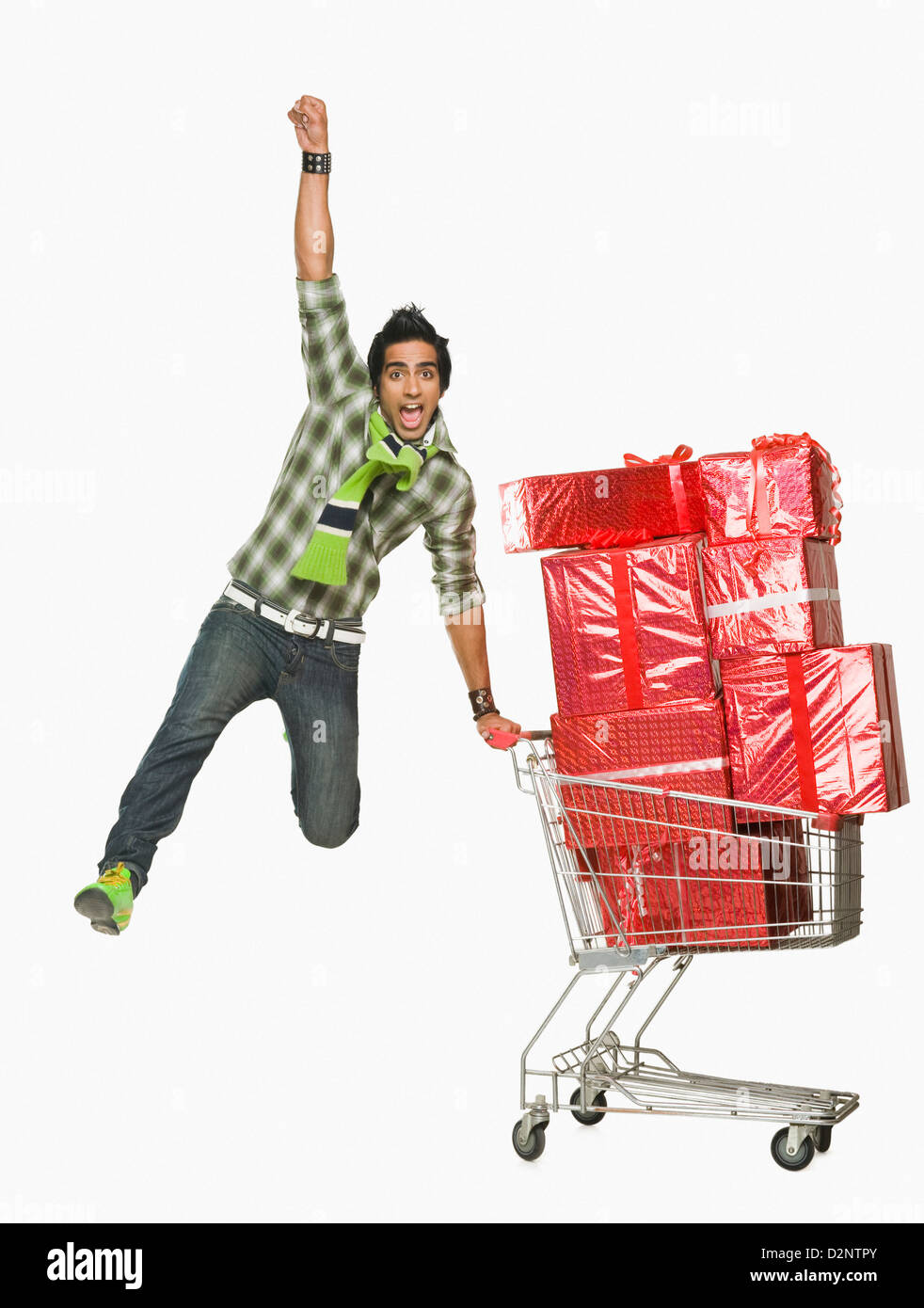 Man leaning against a shopping cart filled with gifts and cheering - Stock Image