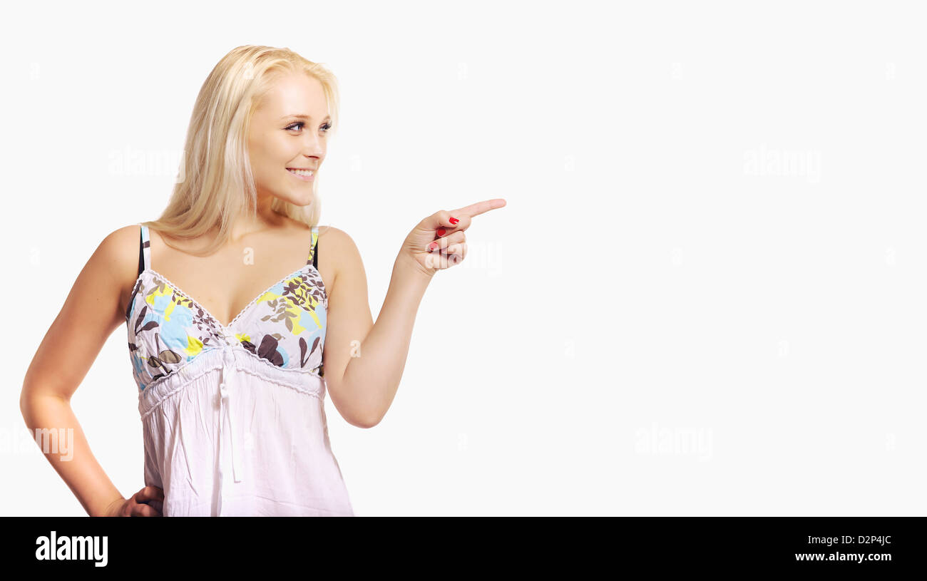 Portrait of a blonde woman pointing at an empty ad space Stock Photo