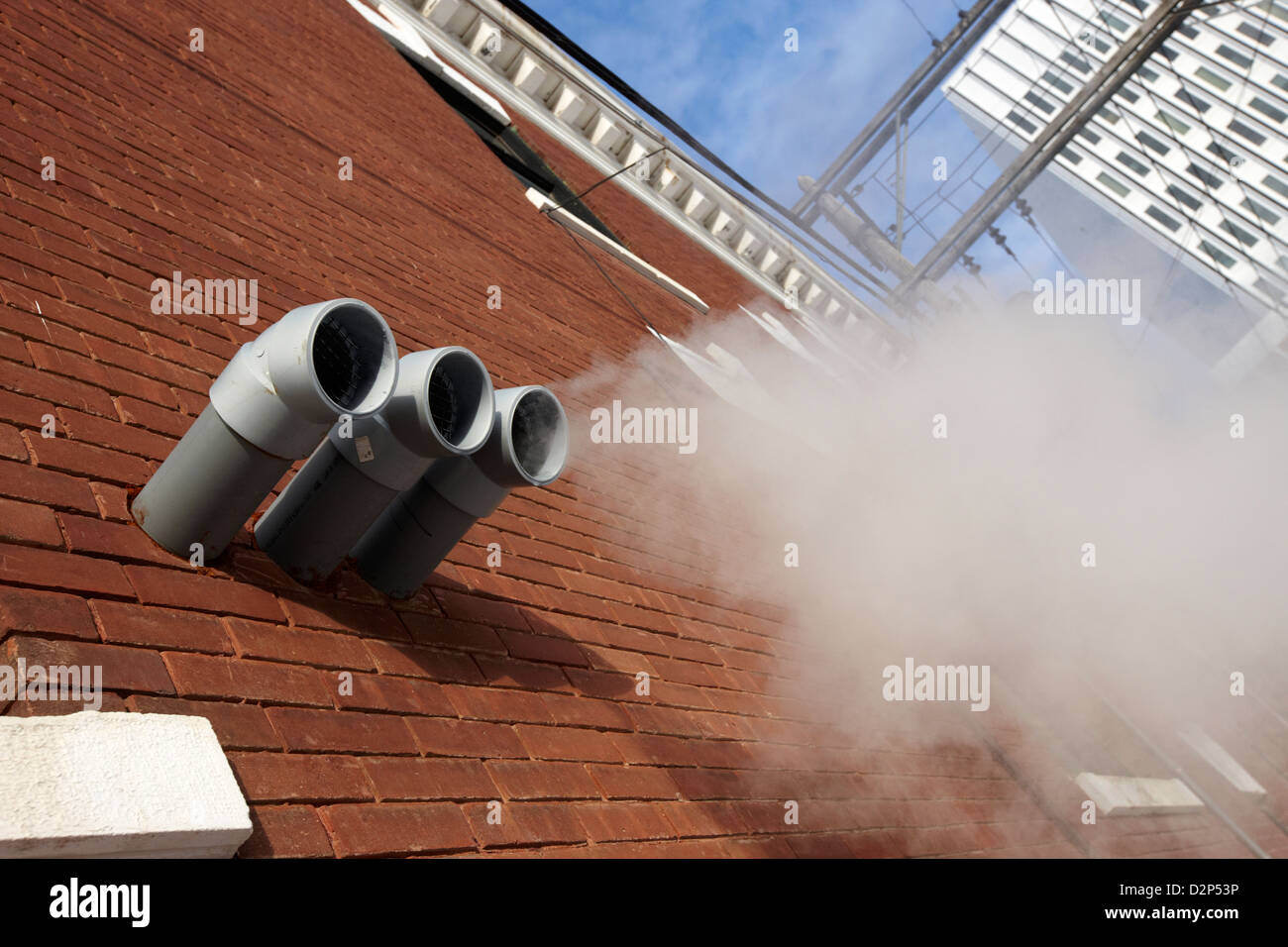 steam venting from plastic exhaust pipes on old brick building downtown Saskatoon Saskatchewan Canada - Stock Image