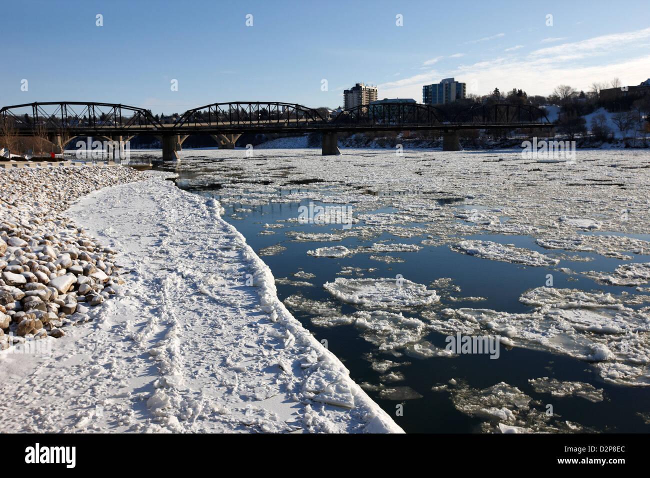 large chunks of floating ice on the south saskatchewan river in winter flowing through downtown Saskatoon Saskatchewan - Stock Image