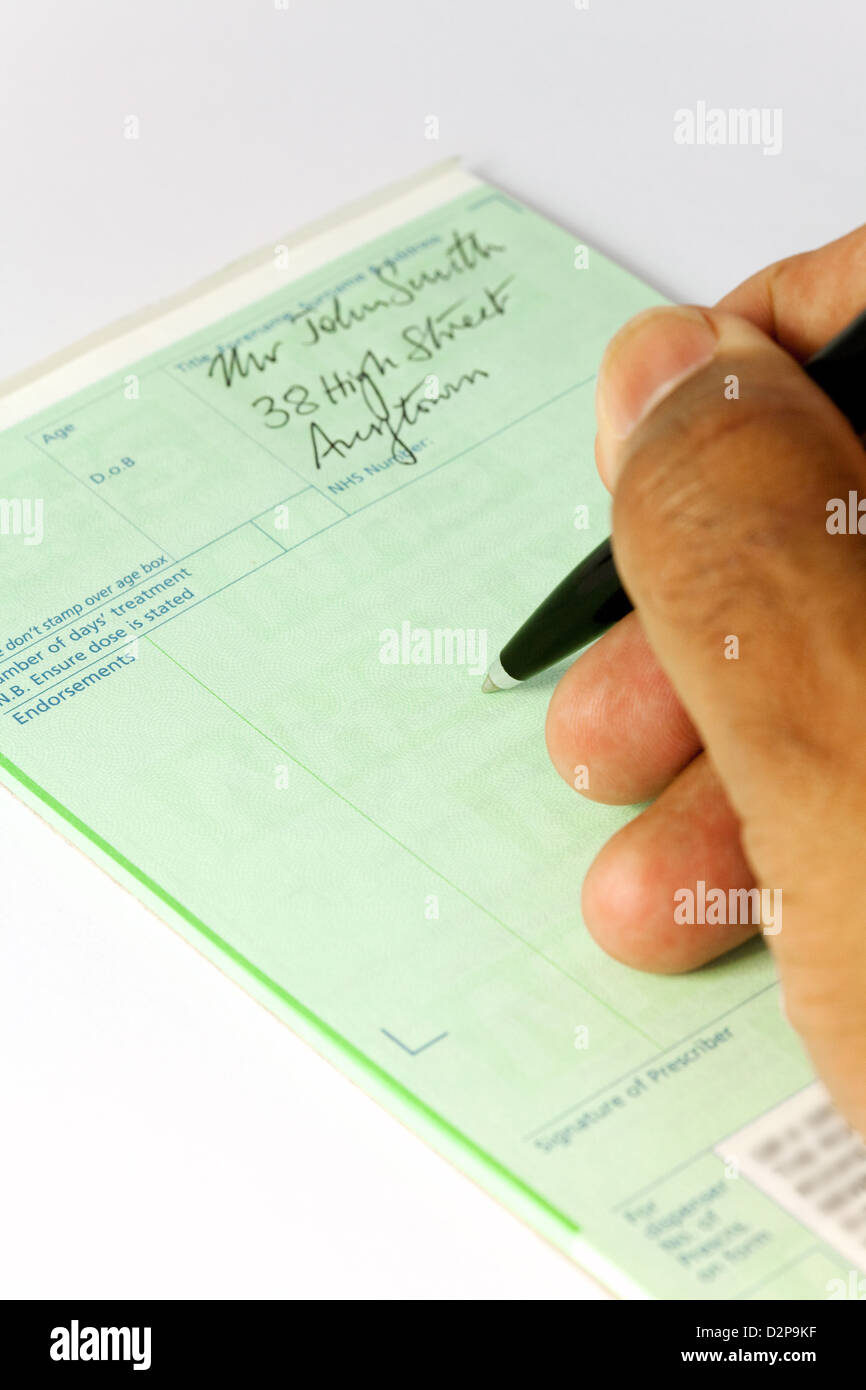 A doctor writing an NHS prescription on a prescription pad, UK - Stock Image