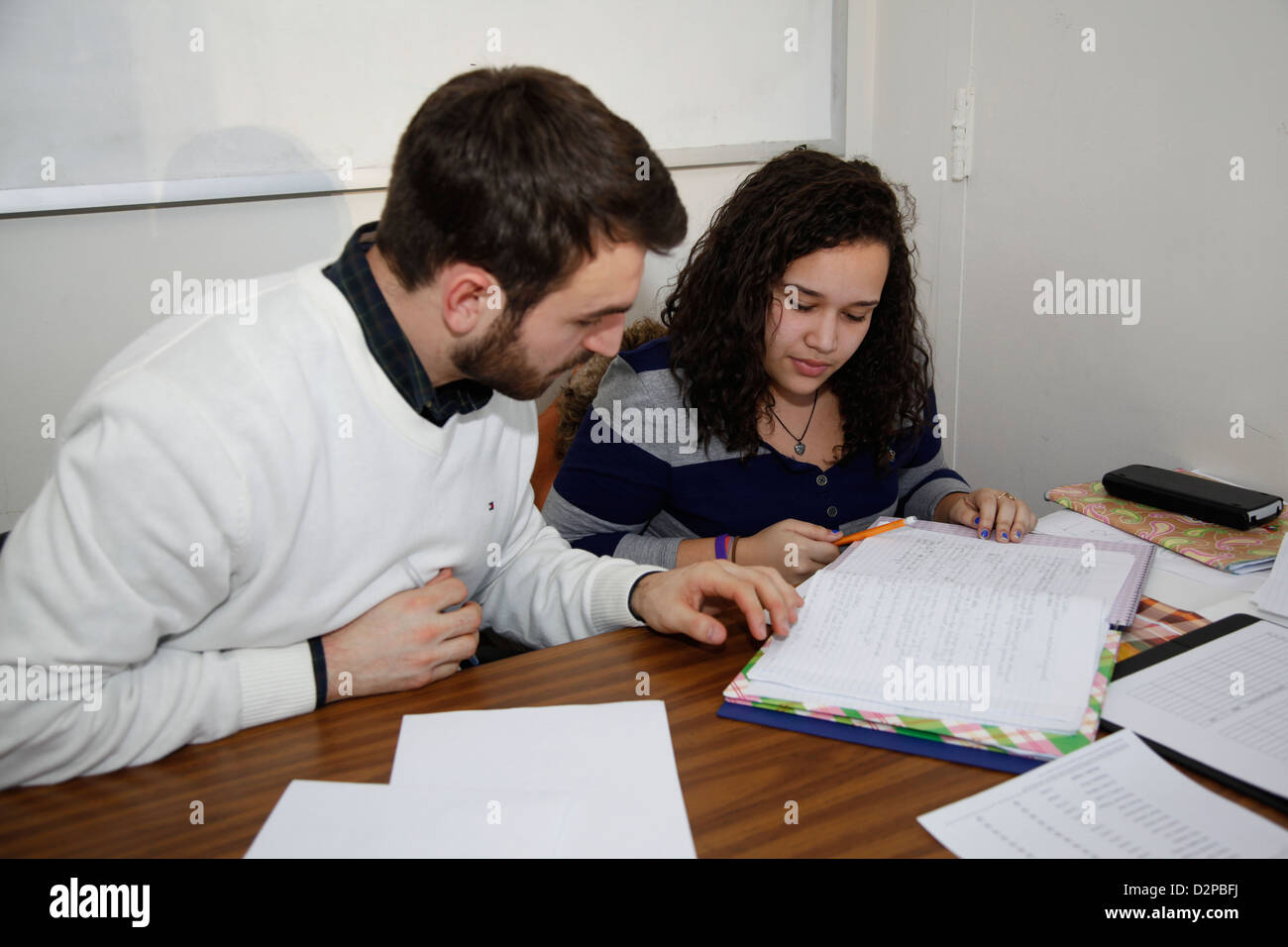 Academic tutor works with a high school student preparing for college. Lower East Side community center, Manhattan. - Stock Image