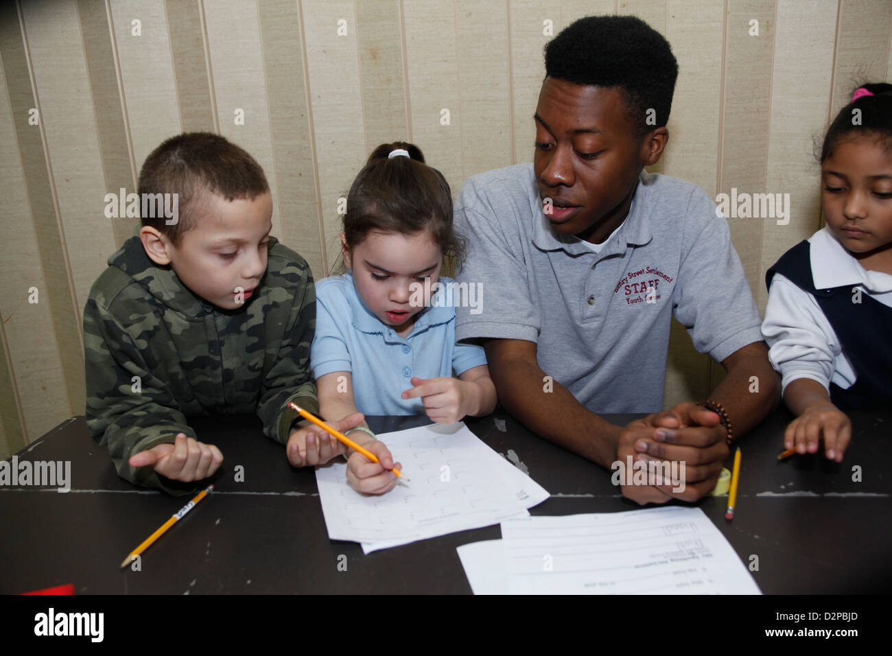 High school age boy works with younger children in an educational after school program in NYC - Stock Image