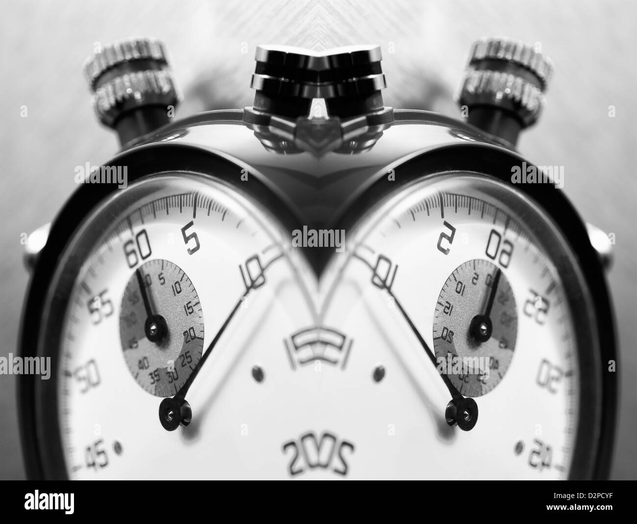 Creative closeup of two stopwatches facing in opposite directions - Stock Image