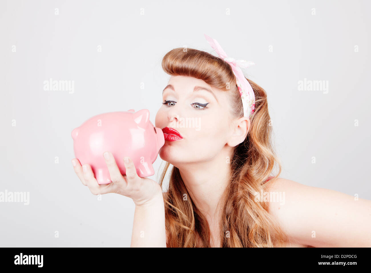 retro pinup woman with piggy bank as saving or spending concept - Stock Image