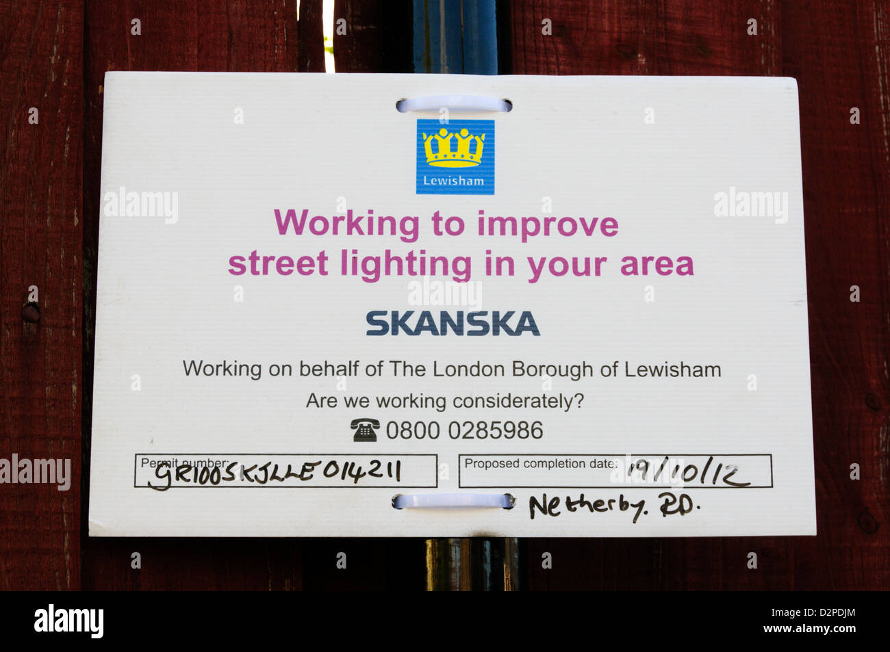 Sign concerning street lighting maintenance by Skanska. - Stock Image